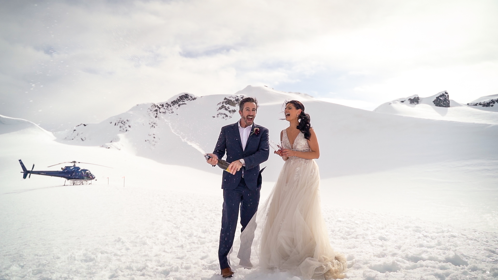 Couple popping champagne on snowy mountaintop