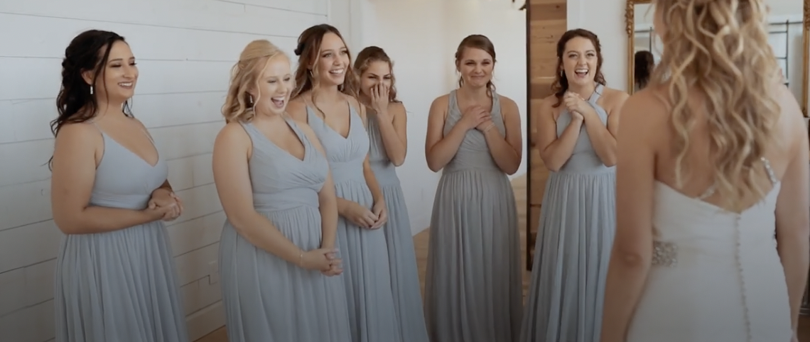 Bridesmaids smiling when they see bride for the first time