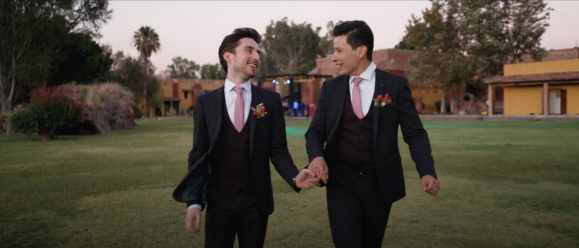 Couple walking and holding hands at romantic, gay Mexican wedding