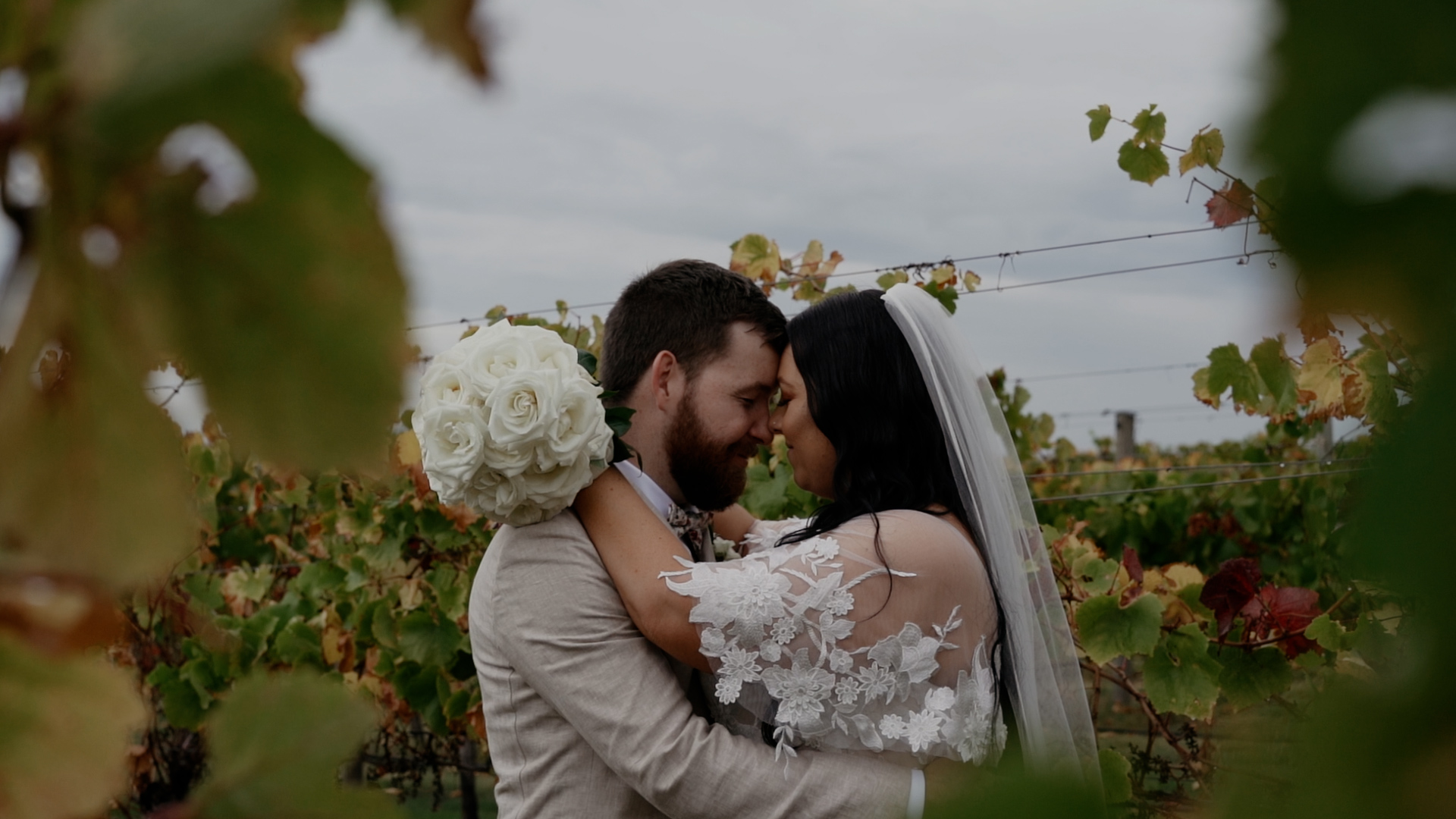 Couple embracing at white vineyard wedding with floral details