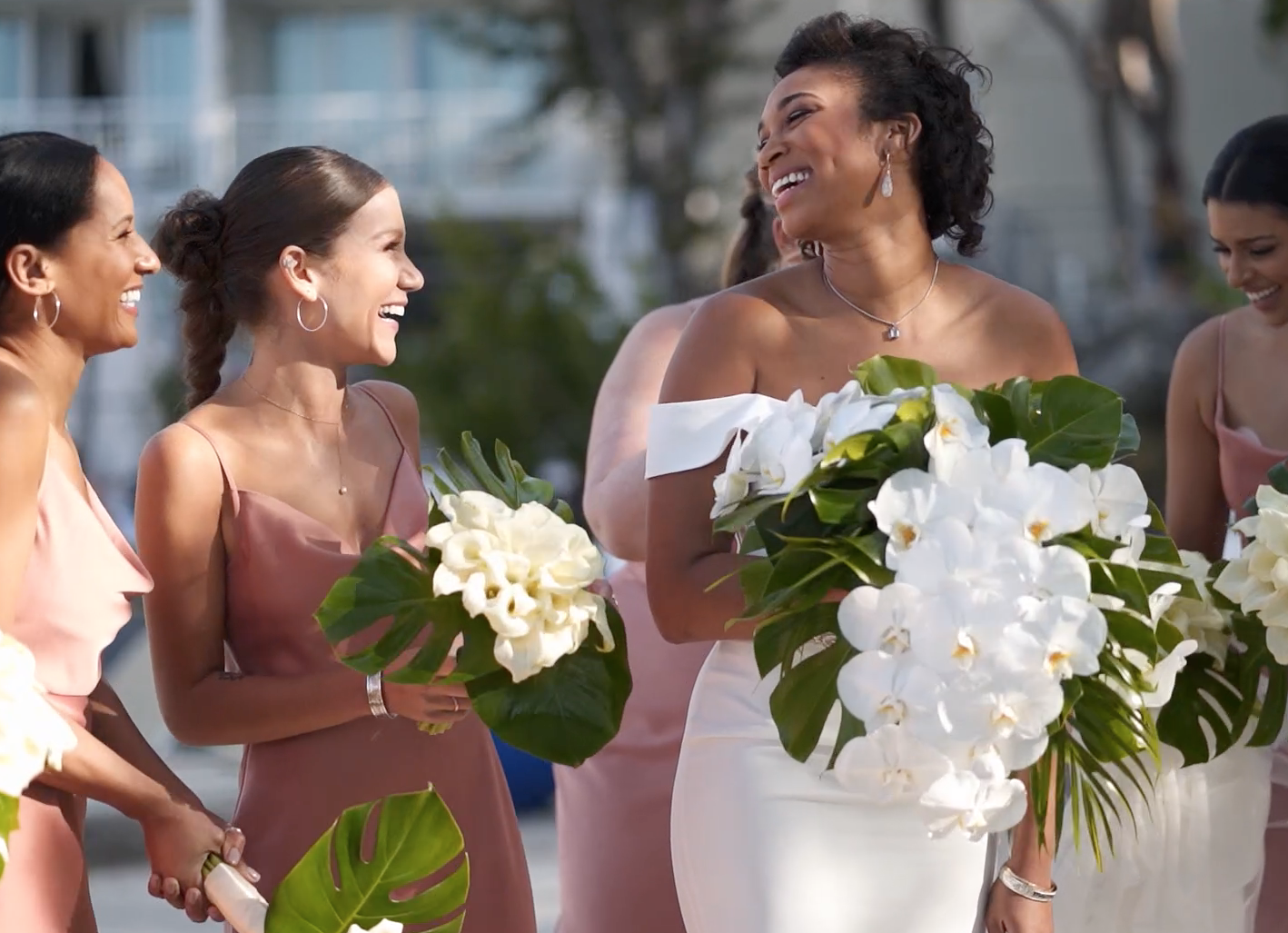 Gorgeous bride with all-white florals and pink bridesmaid gowns