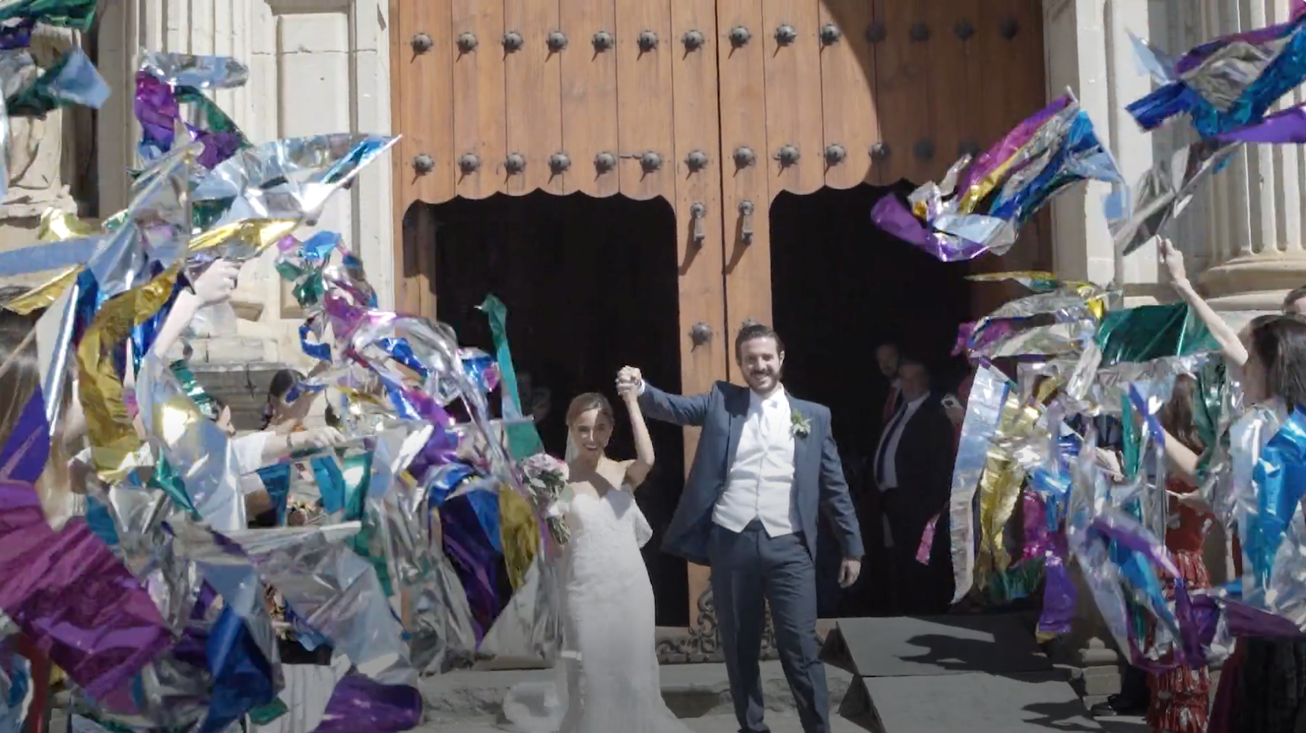 Couple walking out of wedding church ceremony while guests wave streamers