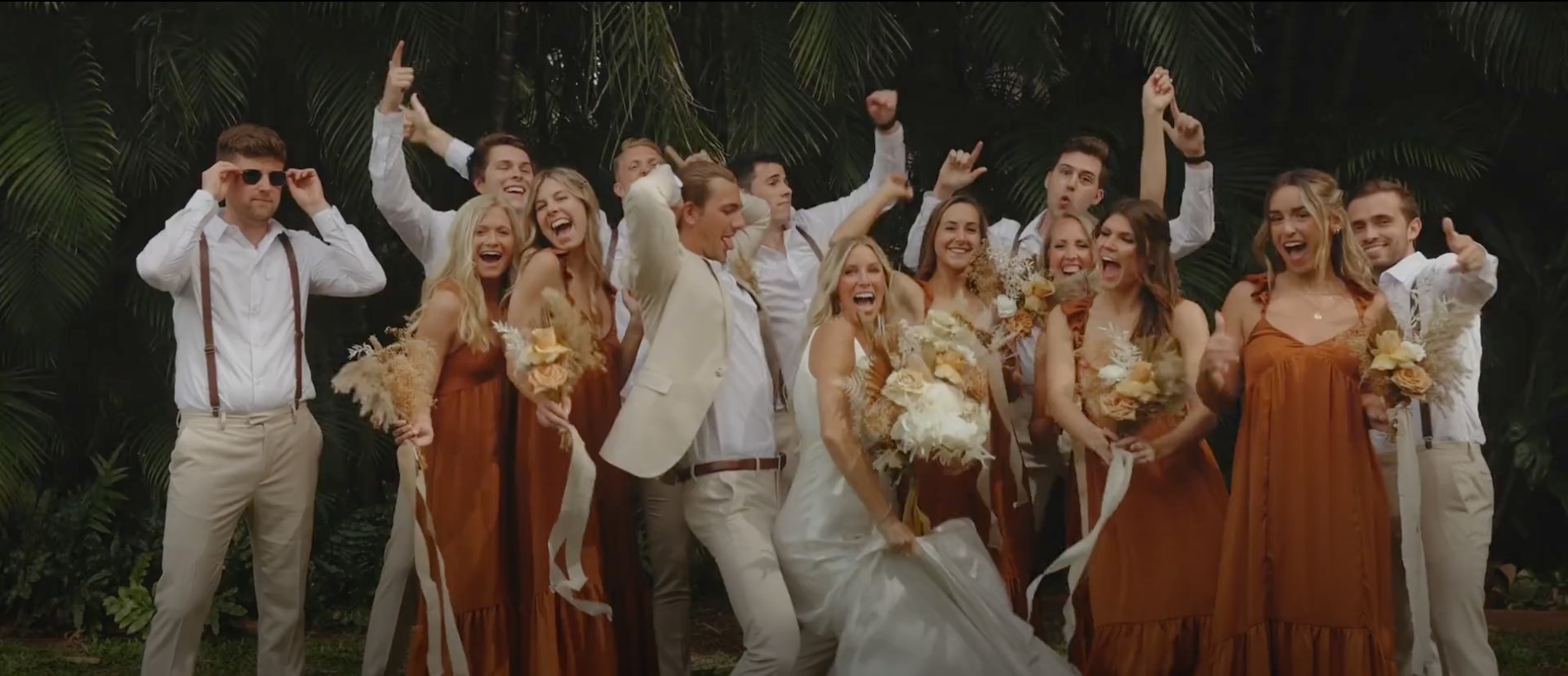Wedding party partying in terracotta wedding dresses and khaki suits