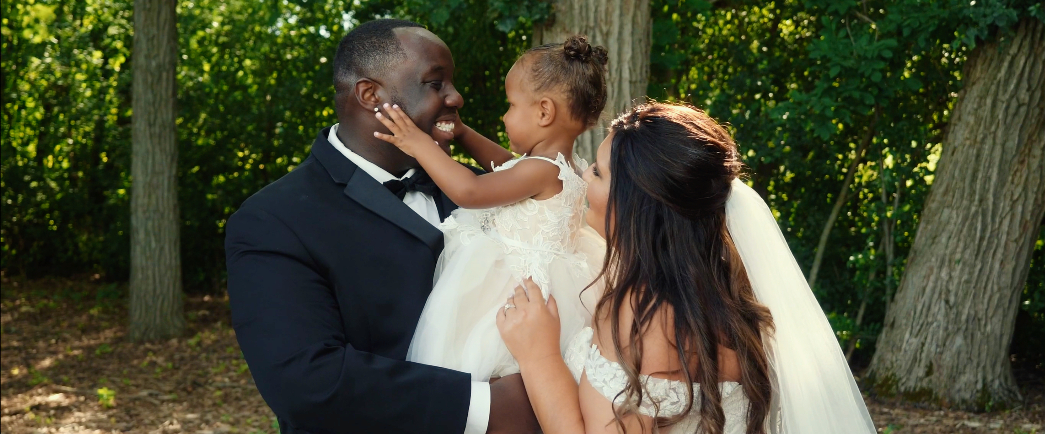 Interracial couple at wedding with their flower girl daughter