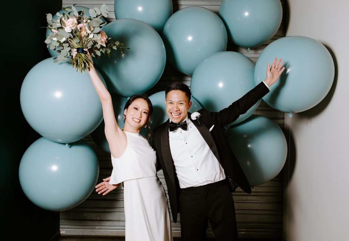 Couple celebrating in front of blue ballon wall